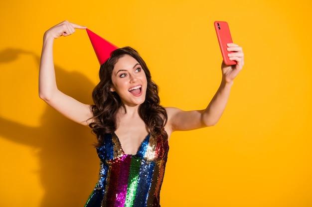 Foto di una ragazza stupita blogger influencer prendere selfie smartphone puntare il dito il suo cono rosso copricapo indossare gonna lucida arcobaleno isolata su sfondo di colore brillante brillante