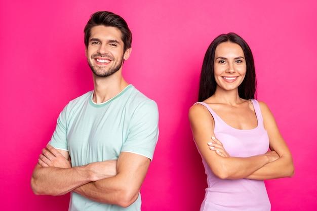 La foto del ragazzo e della signora stupefacenti delle coppie che stanno con i lavoratori affidabili delle braccia incrociate indossano i vestiti casuali isolati fondo di colore rosa vibrante