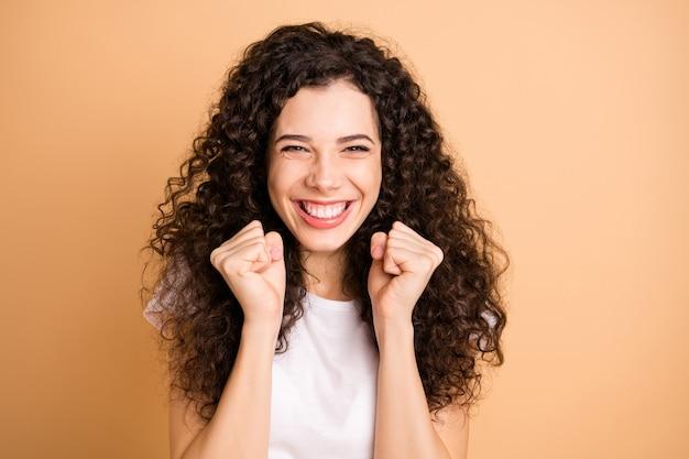 Foto di incredibile signora che ascolta grande pubblicità vendita shopping trionfante alzando i pugni indossare abiti casual bianchi isolati beige colore pastello sfondo