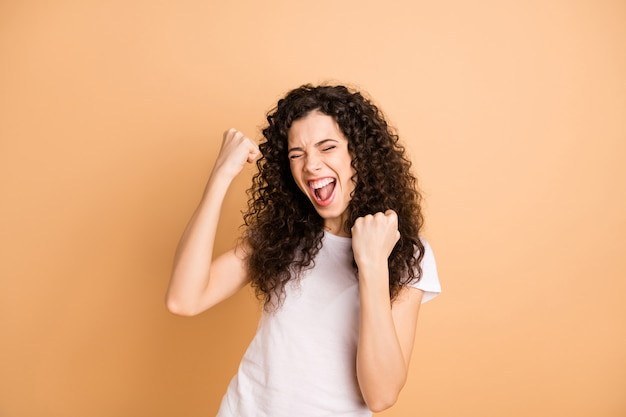Foto di incredibile signora urlante che ascolta grande pubblicità vendita shopping trionfante alzando i pugni indossare abiti casual bianchi isolati beige pastello colore di sfondo