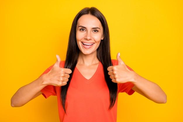 Foto di sorprendente giovane donna che alza i pollici in su esprimendo un atteggiamento positivo accordo consigliando il nuovo prodotto indossare maglietta arancione casual isolato muro di colore giallo