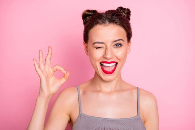 Foto di incredibile giovane ragazza panini divertenti labbra rosse che mostra il simbolo okey lampeggiante occhio civettuolo umore buon lavoro indossare casual canotta grigia isolato colore rosa