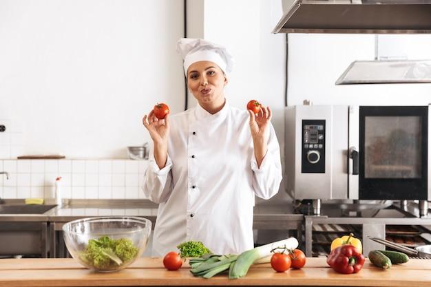 Foto del cuoco unico divertente della donna che indossa il pasto di cottura dell'uniforme bianca con le verdure fresche, nella cucina al ristorante