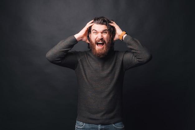 Foto dell'uomo barbuto arrabbiato che sta sopra la testa scura della tenuta e che grida
