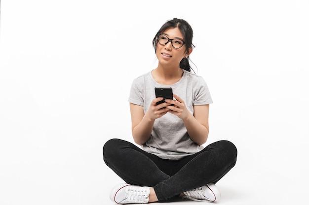 Foto di bella giovane donna asiatica che posa isolata sopra la parete bianca che tiene il telefono cellulare usando.
