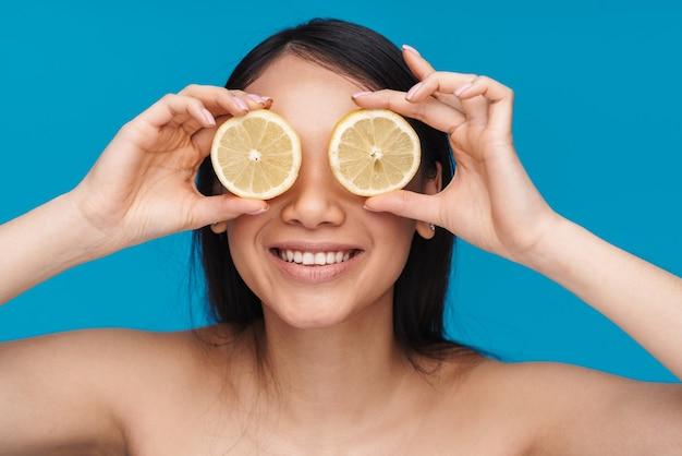 Foto di una giovane donna piuttosto ottimista allegra asiatica in posa isolata sulla parete blu con occhi a cono di limone.