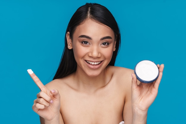 Foto della giovane donna felice ottimista asiatica che posa isolata sulla crema dell'umidità della parete blu della tenuta.