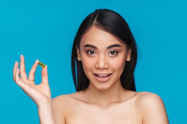 Foto della giovane donna felice ottimista asiatica che posa isolata sulla pillola blu della vitamina della tenuta della parete.