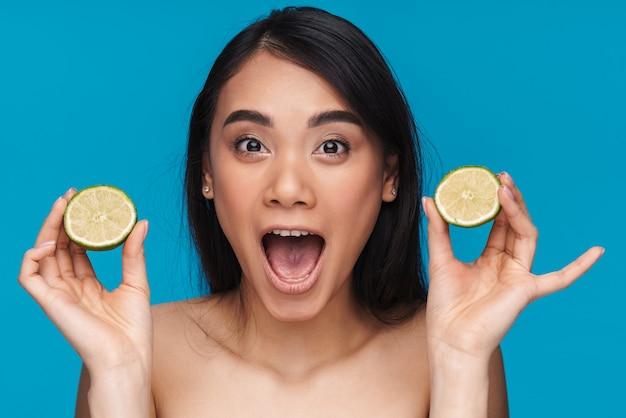 Foto di una giovane donna piuttosto ottimista sorpresa asiatica in posa isolata sulla parete blu con urla di calce.