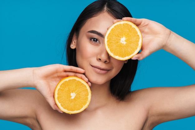 Foto della giovane donna asiatica che posa isolata sulla parete blu con l'arancia.