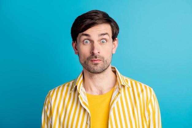 La foto di un ragazzo stupito guarda vedere le terribili notizie del virus corona impressionato indossare abiti a strisce isolati su sfondo blu