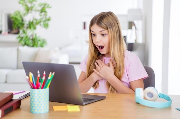 Foto di una ragazza stupita che studia a distanza il computer portatile impressionato da un insegnante di scuola a casa notizie informazioni toccare le mani petto sedersi comfort tavolo scrivania in casa al chiuso