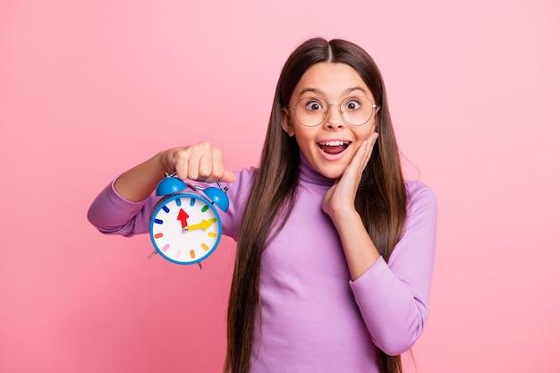 Foto di una bambina stupita che tiene in mano l'orologio che tocca la faccia della mano indossa un maglione viola isolato su uno sfondo di colore pastello