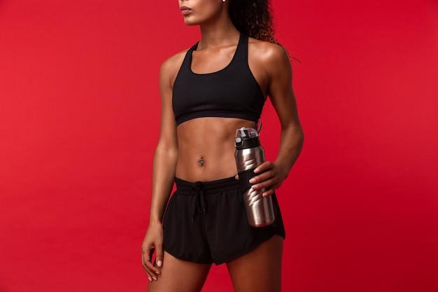 Foto della sportiva afroamericana atletica in bottiglia di acqua nera della tenuta degli abiti sportivi, isolata sopra la parete rossa