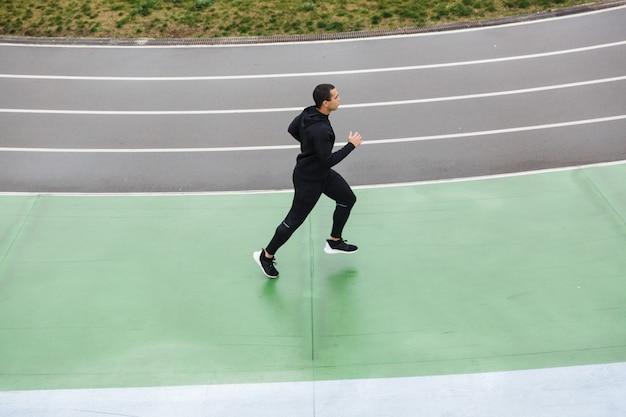 Foto di un forte sportivo atletico in tuta da ginnastica che corre mentre si allena allo stadio dopo la pioggia