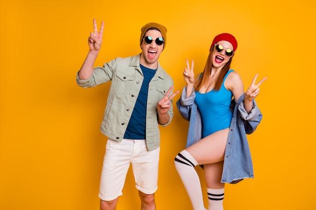 Foto di attraente signora pazza ragazzo giovane marito moglie turisti trascorrono le vacanze insieme mostrano simboli v-segno indossare abiti estivi luminosi casual vestito isolato sfondo di colore giallo brillante