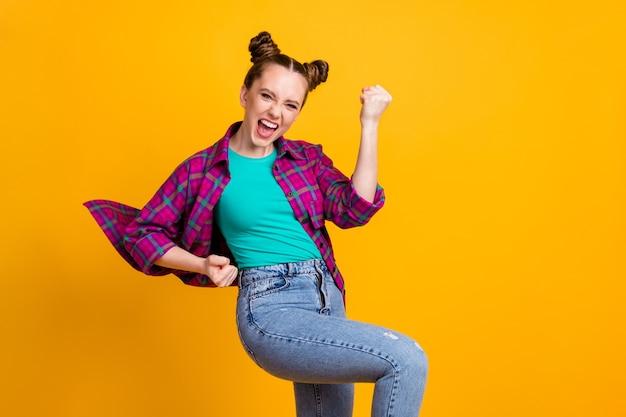 Foto di attraente eccitata pazza adolescente signora due panini divertenti buon umore tifo squadra di calcio sostenitore dello sport alzare i pugni indossare casual camicia a quadri isolato giallo brillante colore sfondo