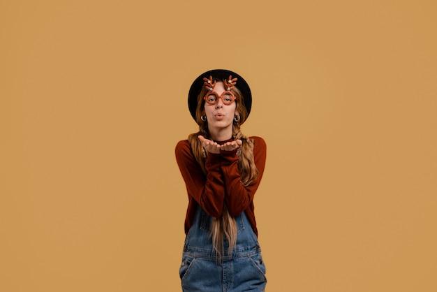 La foto dell'agricoltore femminile attraente si alza, indossa occhiali divertenti e invia un bacio d'aria. la donna bianca indossa tuta in denim e cappello isolato su sfondo marrone di colore.