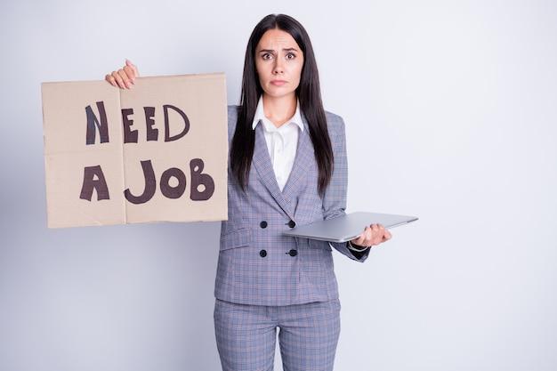 Foto di attraente licenziata triste terrorizzata signora tenere cartone cartellone cercare lavoro freelance offerta di lavoro bisogno di soldi tenere netbook abbigliamento formale abito scozzese isolato colore grigio sfondo