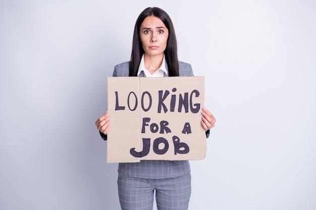 Foto di attraente licenziata triste terrorizzata signora tenere cartone cartellone cercare lavoro accettare accettare qualsiasi offerta proposta di lavoro bisogno di soldi per vivere abbigliamento formale abito scozzese isolato colore grigio sfondo