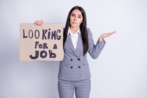 Foto di attraente licenziato arrabbiato manager signora attesa cartone cartellone cercare lavoro accettare di accettare qualsiasi offerta proposta di lavoro scrollare le spalle abbigliamento formale abito scozzese isolato colore grigio sfondo