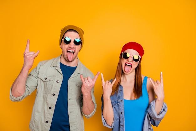 Foto di attraente funky bella signora ragazzo giovane coppia tempo libero insieme fresca gioventù che mostra le corna bastone lingua indossare abiti estivi casuali isolato sfondo di colore giallo brillante
