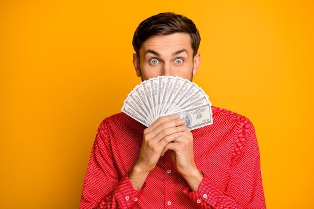 La foto del ragazzo divertente attraente tiene il fan dei dollari usa nasconde la bocca sorriso pazzo persona ricca indossa vestiti alla moda con cravatta a farfalla rossa