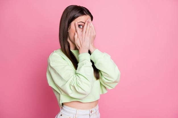 Foto di una donna attraente e divertente che chiude gli occhi braccia sbirciando sguardo voglio sapere segreto persona curiosa indossare casual verde raccolto felpa pullover isolato rosa pastello colore sfondo