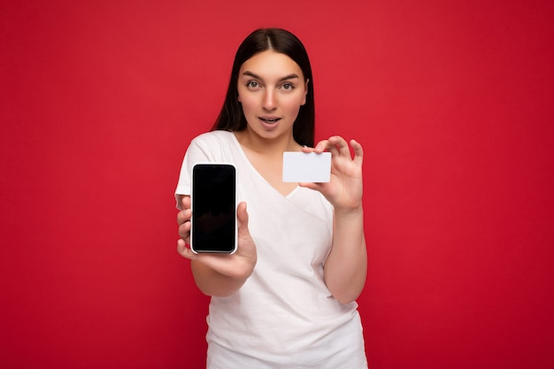 Foto di una giovane donna bruna attraente e felice che indossa una maglietta bianca casual isolata su rosso