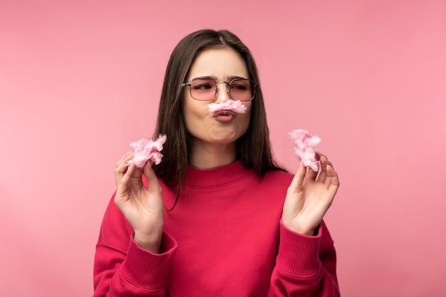 La foto della signora attraente con gli occhiali gioca con lo zucchero filato, si diverte. indossa pantaloni bianchi casual maglione rosa isolato sfondo di colore rosa.