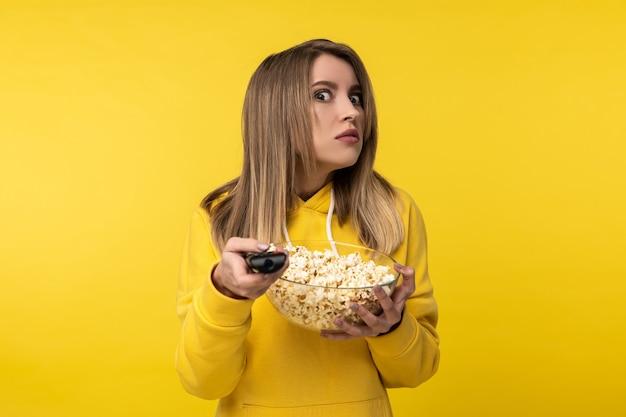 La foto della signora attraente tiene il telecomando della tv e un piatto di popcorn, con la faccia scontenta cerca di girare un canale. indossa una felpa con cappuccio gialla casual, sfondo di colore giallo isolato.