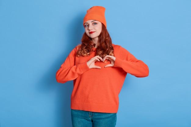 La foto di una donna attraente che fa figura a forma di cuore con le dita, ha uno stato d'animo romantico, indossa jeans, cappello e maglione arancione casual