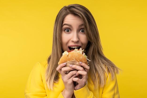 La foto della signora attraente posa in un modo felice cerca di mordere l'hamburger. indossa una felpa con cappuccio gialla casual, sfondo di colore giallo isolato.