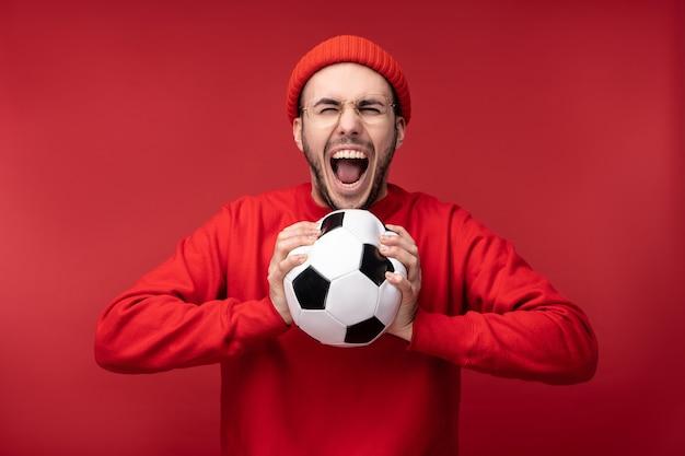 Foto di un uomo attraente con la barba in occhiali e vestiti rossi. l'uomo felice tiene la palla e prova a spremerlo, isolato su sfondo rosso.