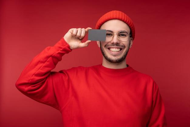 Foto di un uomo attraente con la barba in occhiali e vestiti rossi. l'uomo felice tiene la carta di credito davanti al viso, isolato su sfondo rosso.