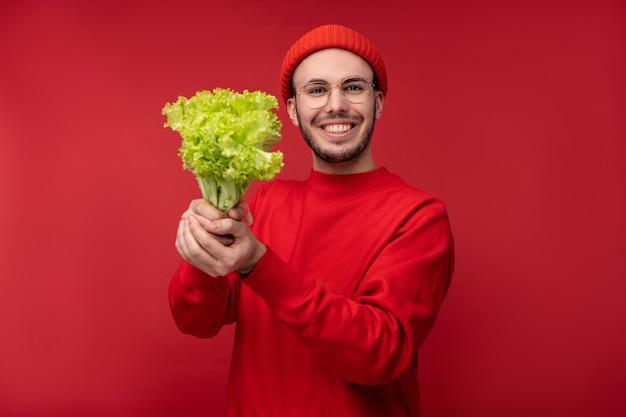 Foto di un uomo attraente con la barba in occhiali e vestiti rossi. il maschio tiene insalata, mostra la preferenza alle verdure, isolate sopra fondo rosso.
