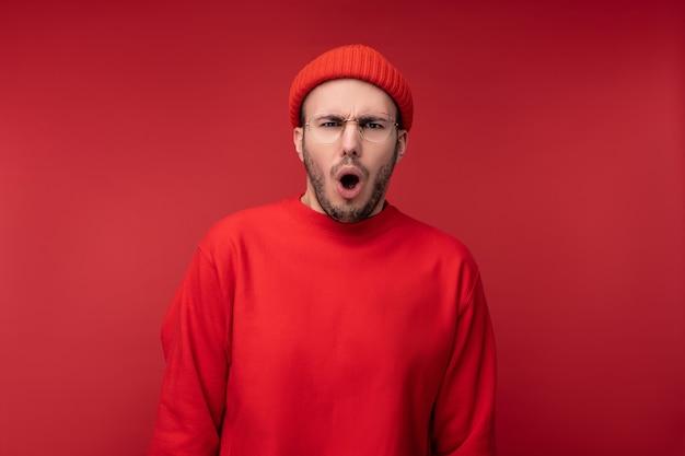 Foto di un uomo attraente con la barba in occhiali e vestiti rossi. maschio scioccato e bocca aperta, isolato su sfondo rosso.