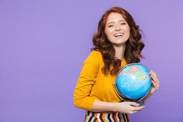 Foto della donna attraente della testarossa che porta i vestiti gialli che sorridono e che tengono il globo della terra sopra la porpora