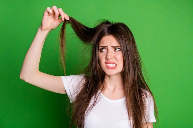 Foto di una donna attraente e triste che indossa una maglietta bianca che tiene i capelli con le estremità asciutte sullo sfondo di colore verde isolato