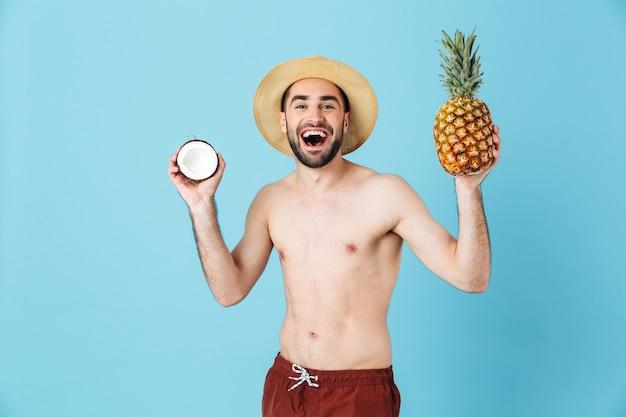 Foto di un attraente turista a torso nudo che indossa un cappello di paglia che sorride mentre tiene in mano frutti esotici isolati sopra il blu