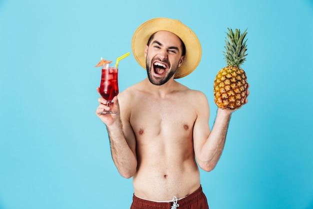 Foto di un attraente turista senza camicia che indossa un cappello di paglia che sorride mentre tiene in mano ananas e cocktail isolati