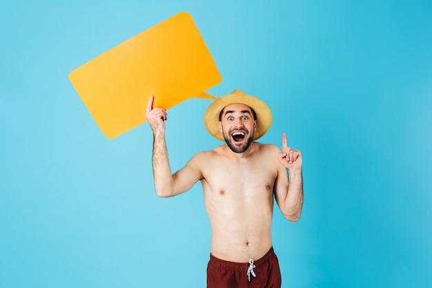 Foto di un attraente turista a torso nudo che indossa un cappello di paglia che sorride mentre tiene in mano un cartello giallo copyspace isolato su blu