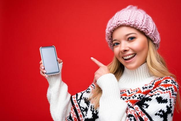 Foto di una giovane donna bionda sorridente attraente che indossa un cappello lavorato a maglia caldo e un maglione caldo invernale