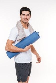 Foto di sportivo attraente con asciugamano in palestra in piedi sul muro bianco.