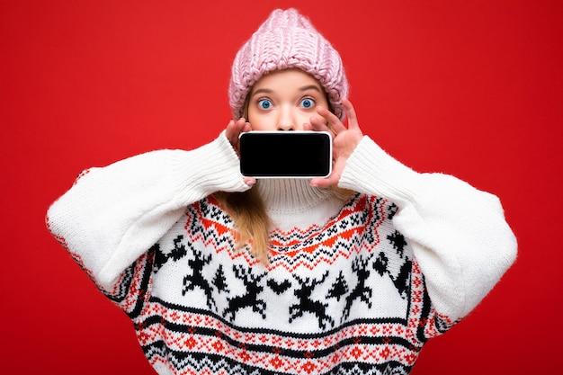 Foto di giovane donna bionda sorpresa attraente che porta cappello lavorato a maglia caldo e maglione caldo di inverno