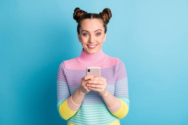 Foto di attraente signora adolescente due bei panini buon umore libero professionista tenere le mani del telefono in chat amici seguaci che rispondono indossare maglione a righe casual isolato sfondo di colore blu