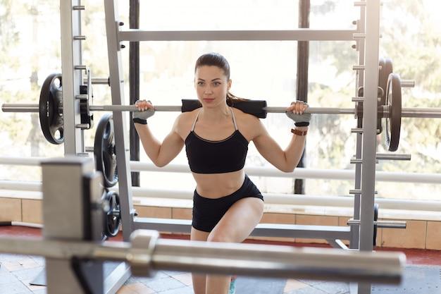Foto della donna attraente che fa esercizio di affondo con il carico del bilanciere sulla parte posteriore
