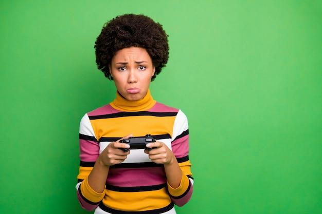 Foto di cattivo umore pelle scura signora ondulata giocare ai videogiochi mani joystick perdente giocatore terribile pianto dolore indossare maglione a righe casual