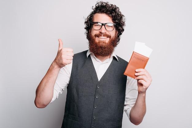 Foto di un uomo barbuto casual che mostra pollice in alto e il suo passaporto con i biglietti