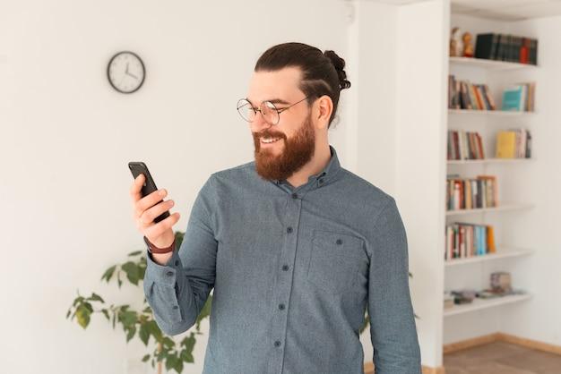 Foto di uomo barbuto in casual utilizza lo smartphone in ufficio
